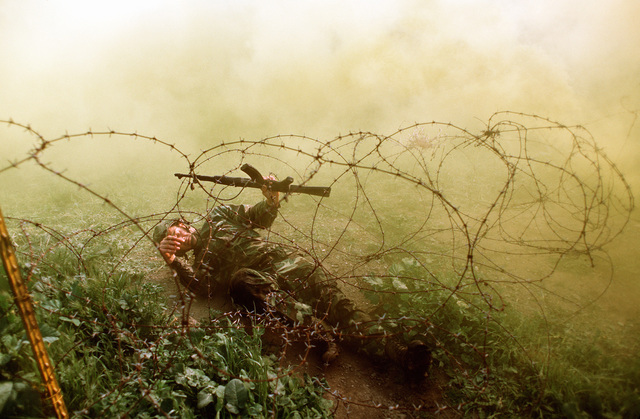 A Navy corpsman uses an AK-47 assault rifle to help him crawl under barbed wire on the obstacle course during a simulated firefight. He is undergoing combat training at the Field Medical Service School