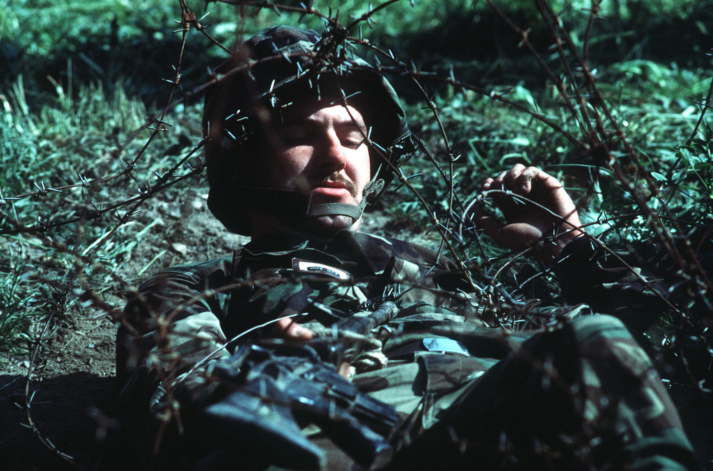 A Navy corpsman uses his M-16A1 rifle to help him crawl under barbed wire on the obstacle course during a simulated firefight. He is undergoing combat training at the Field Medical Service School