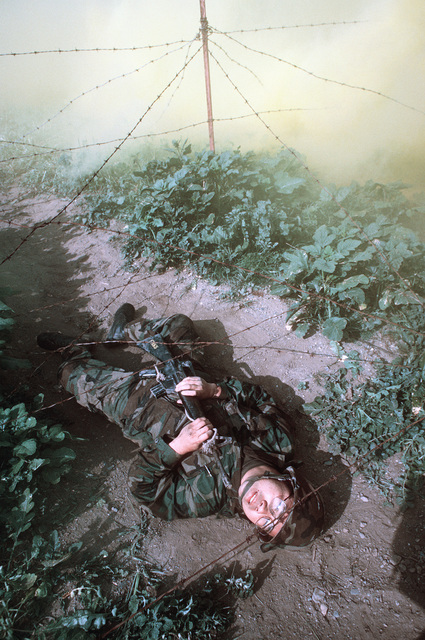 A Navy corpsman uses his M16A rifle to help him crawl under barbed wire on the obstacle course during a simulated firefight. He is undergoing combat training at the Field Medical Service School