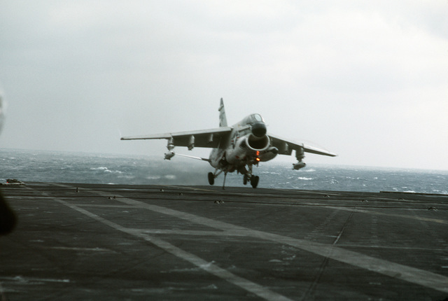 A right side view of A-7 Corsair II aircraft coming in for an arrested landing aboard the aircraft carrier USS MIDWAY (CV 41)