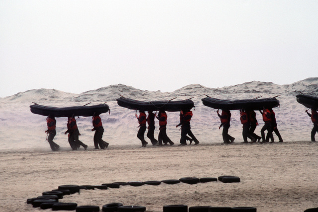"""A U.S. Navy Basic Underwater Demolition/Sea-Air-Land (SEAL) (BUD/S) trainees carry rubber boats across the sand during a """"hell week"""" exercise. Phase I of BUD/S training concludes with """"hell week,"""" when students' physical, emotional and mental abilities are tested under adverse conditions"""