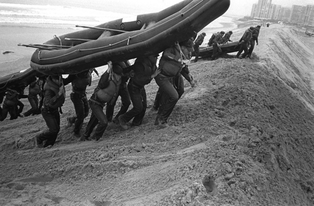 """A U.S. Navy Basic Underwater Demolition/Sea-Air-Land (SEAL) (BUD/S) trainees carry rubber boats up a sand dune during a """"hell week"""" exercise. Phase I of BUD/S training concludes with """"hell week,"""" when students' physical, emotional and mental abilities are tested under adverse conditions"""
