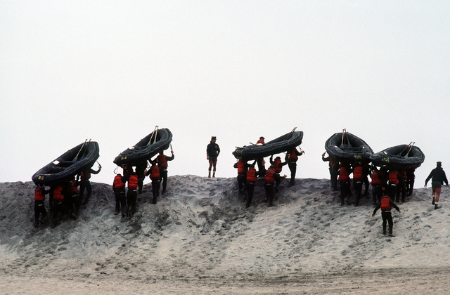 """A U.S. Navy Basic Underwater Demolition/Sea-Air-Land (SEAL) (BUD/S) trainees carry rubber boat boats up a sand dune during a """"hell week"""" exercise. Phase I of BUD/S training concludes with """"hell week,"""" when students' physical, emotional and mental abilities are tested under adverse conditions"""