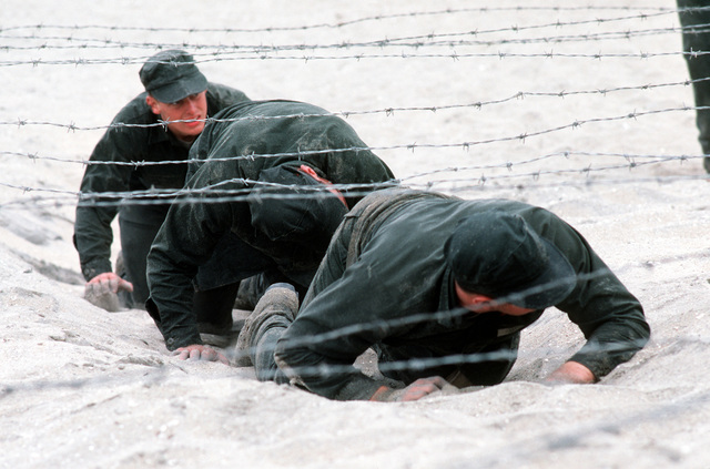 """A U.S. Navy Basic Underwater Demolition/Sea-Air-Land (SEAL) (BUD/S) trainees crawl under a barbed wire obstacle during a """"hell week"""" exercise. Phase I of BUD/S training concludes with """"hell week,"""" when students' physical, emotional and mental abilities are tested under adverse conditions"""