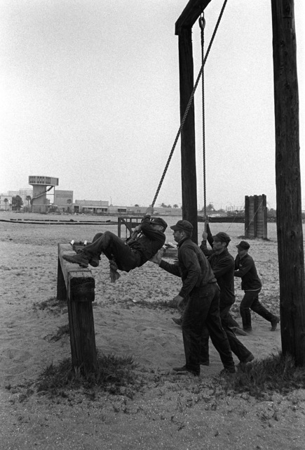 """A U.S. Navy Basic Underwater Demolition/Sea-Air-Land (SEAL) (BUD/S) trainees cross a rope swing on the obstacle course during a """"hell week"""" exercise. Phase I of BUD/S training concludes with """"hell week,"""" when students' physical, emotional and mental abilities are tested under adverse conditions"""