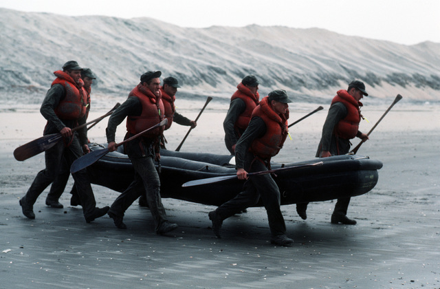 """A U.S. Navy Basic Underwater Demolition/Sea-Air-Land (SEAL) (BUD/S) trainees launch a rubber boat into the surf during a """"hell week"""" exercise. Phase I of BUD/S training concludes with """"hell week,"""" when students' physical, emotional and mental abilities are tested under adverse conditions"""