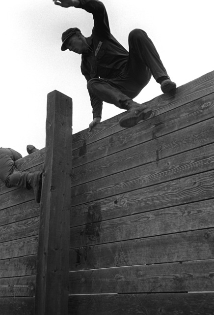 """A U.S. Navy Basic Underwater Demolition/Sea-Air-Land (SEAL) (BUD/S) trainees leap off a wall on the obstacle course during a """"hell week"""" exercise. Phase I of BUD/S training concludes with """"hell week,"""" when students' physical, emotional and mental abilities are tested under adverse conditions"""