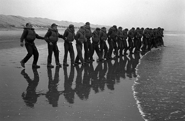 """A U.S. Navy Basic Underwater Demolition/Sea-Air-Land (SEAL) (BUD/S) trainees link arms and enter the surf during a """"hell week"""" exercise. Phase I of BUD/S training concludes with """"hell week,"""" when students' physical, emotional and mental abilities are tested under adverse conditions"""