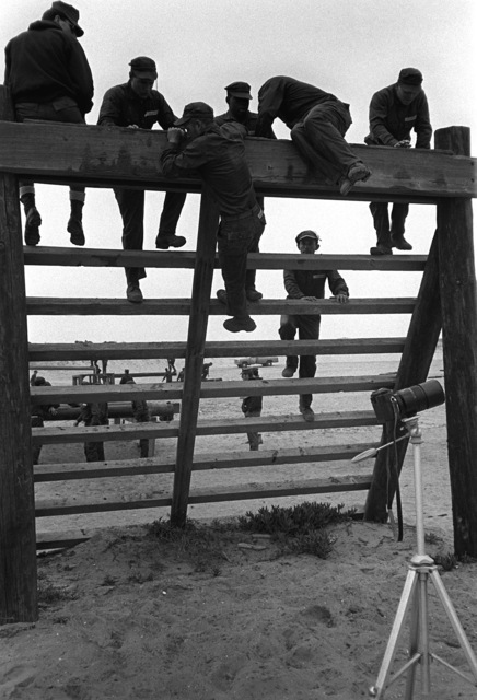 """A U.S. Navy Basic Underwater Demolition/Sea-Air-Land (SEAL) (BUD/S) trainees scale an obstacle during a """"hell week"""" exercise. Phase I of BUD/S training concludes with """"hell week,"""" when students' physical, emotional and mental abilities are tested under adverse conditions"""
