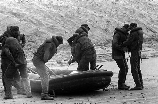 """A U.S. Navy Basic Underwater Demolition/Sea-Air-Land (SEAL) (BUD/S) trainees secure their life jackets prior to launching a rubber boat into the surf during a """"hell week"""" exercise. Phase I of BUD/S training concludes with """"hell week,"""" when students' physical, emotional and mental abilities are tested under adverse conditions"""
