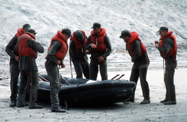 """A U.S. Navy Basic Underwater Demolition/Sea-Air-Land (SEAL) (BUD/S) trainees secure their life jackets prior to laundching a rubber boat during a """"hell week"""" exercise. Phase I of BUD/S training concludes with """"hell week,"""" when students' physical, emotional and mental abilities are tested under adverse conditions"""