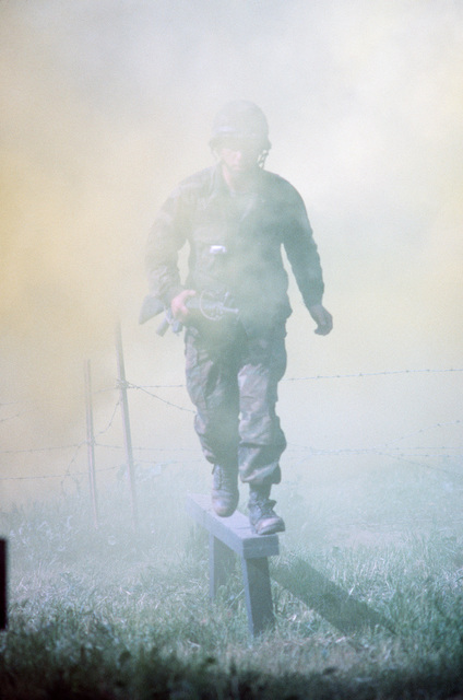 Armed with an M16A rifle, a Navy corpsman runs a smoke-filled obstacle course during a simulated firefight. He is undergoing combat training at the Field Medical Service School