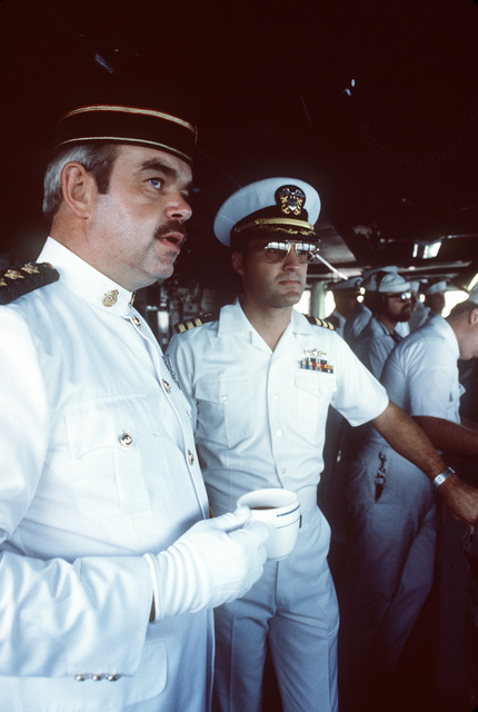 Commander James Carter, executive officer, right, hosts a Royal Brunei Armed Forces officer on the bridge of the guided missile destroyer USS HENRY B. WILSON (DDG 7). The WILSON is the first US Navy ship to visit Brunei since the USS CONSTITUTION in 1845. PHOTO from March 1985 All Hands Magazine