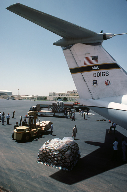 Food and supplies are unloaded from a C-141B Starlifter aircraft and transferred to waiting trucks by members of the 6th Military Airlift Squadron and CARE during Ethiopian relief operations. The supplies will be moved to a distribution center and given to the needy