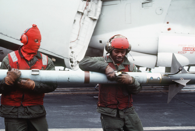Navy personnel prepare to unload an AIM-9 Sidewinder missile from an aircraft aboard the aircraft carrier USS MIDWAY (CV 41)