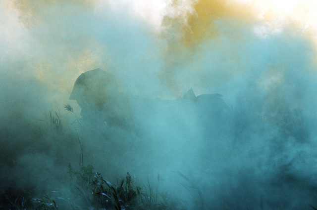 Obscured by smoke, a US Navy corpsman crawls along the ground on the obstacle course during a simulated firefight. He is undergoing combat training at the Field Medical Service School