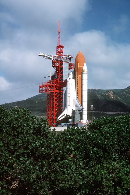 """Overall view of Space Shuttle Enterprise in launch position on the Space Launch Complex (SLC) #6, commonly known as """"SLICK 6"""", during the ready-to-launch checks to verify launch procedures. Exact Date Shot Unknown"""