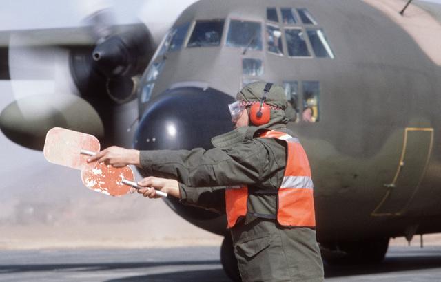 Senior AIRMAN (SRA) Robert H. Allen, 60th Field Maintenance Squadron, marshalls a C-130E Hercules aircraft onto the runway at Yoju Airfield during Exercise TEAM SPIRIT '85
