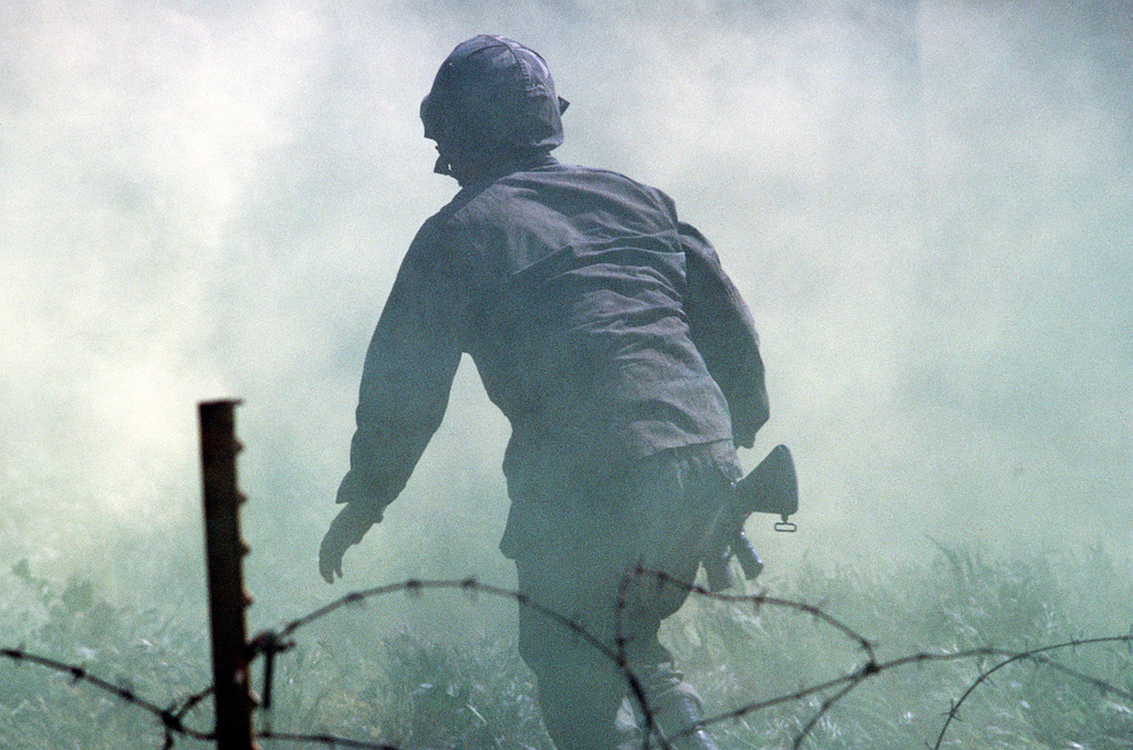 Smoke obscures the area as a Navy corpsman runs the obstacle course during a simulated firefight. He is undergoing combat training at the Field Medical Service School. (Exact Date Shot Unknown)