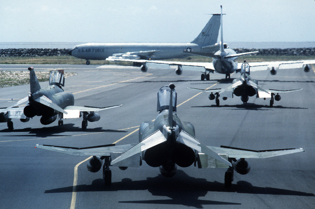 Two KC-135 Stratotanker aircraft taxi onto the runway as three 563rd Tactical Wing F-4G Wild Weasel Phantom II aircraft stand by on the flight line during Exercise Team Spirit '85