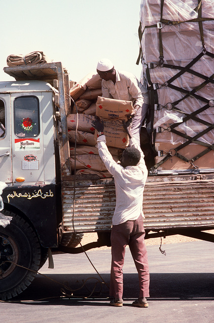 Two Sudanese workers load a truck with food and supplies that were flown into the airport aboard a 6th Military Airlift Squadron aircraft during Ethiopian relief operations. The supplies will be moved to a distribution center and given to the needy