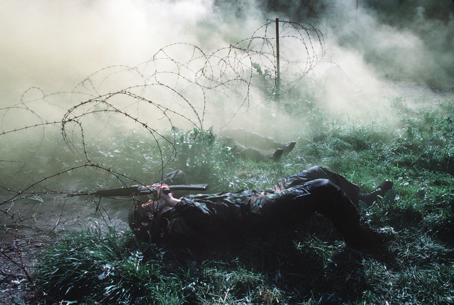 US Navy corpsmen crawl under barbed wire on a smoke-filled obstacle course during a simulated firefight. The corpsman in the foreground is using an M16A1 rifle to push the wire out of his path. They are undergoing combat training at the Field Medical Service School