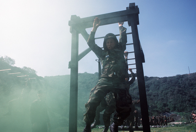 US Navy corpsmen run the obstacle course during a simulated firefight. They are undergoing combat training at the Field Medical Service School