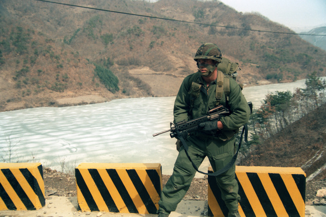 SPECIALIST Fourth Class (SPC 4) Joe Thompson, a rifleman of Company B, 1ST Battalion, 5th Infantry, 25th Infantry Division armed with an M-203 40mm grenade launcher equipped M-16 rifle, advances past a frozen lake during the joint U.S./South Korean Exercise TEAM SPIRIT`85