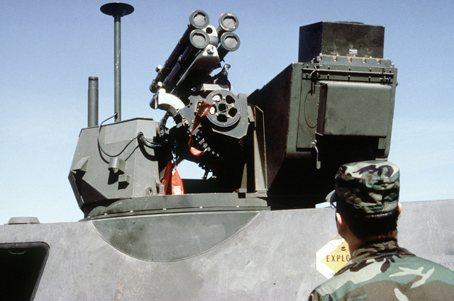 A Marine looks at the turret of an LAV-25 light armored vehicle equipped with a GAU-13/A 30mm lightweight gun and an FIM-92A Stinger portable anti-aircraft missile
