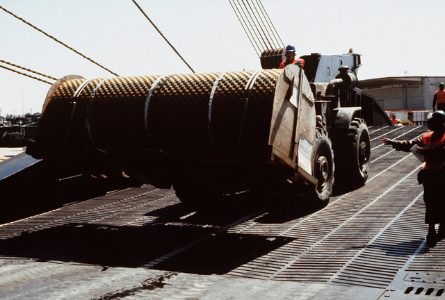 A 7231M forklift truck carries a roll of portable roadway up the stern loading ramp of the Waterman class maritime prepositioning ship SS PFC. EUGENE A. OBREGON. Equipment of the 6th Marine Amphibious Brigade is being loaded aboard the ship