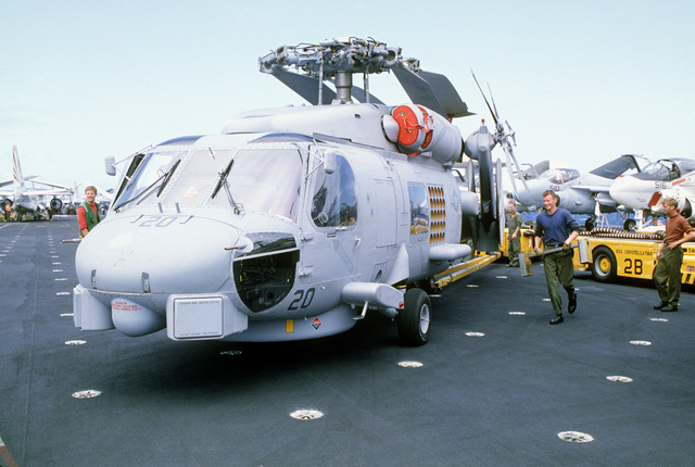 A flight crewman aboard the aircraft carrier USS CONSTELLATION (CV 64) prepares to place a chock under the left front wheel on an SH-60B Seahawk light airborne multi-purpose system (LAMPS III) helicopter. The SH-60B is assigned to Light Helicopter Anti-submarine Squadron 43 (HSL-43)