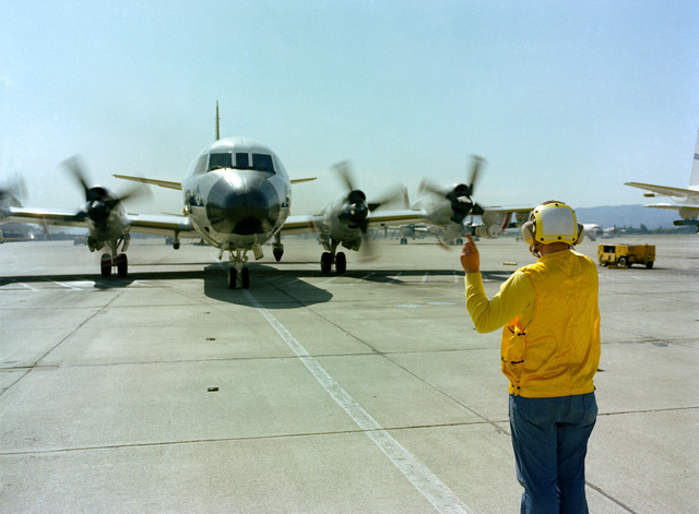 A line crewman directs the pilot of a Patrol Squadron 50 (VP-50) P-3C Orion aircraft during the annual mine readiness certification inspection