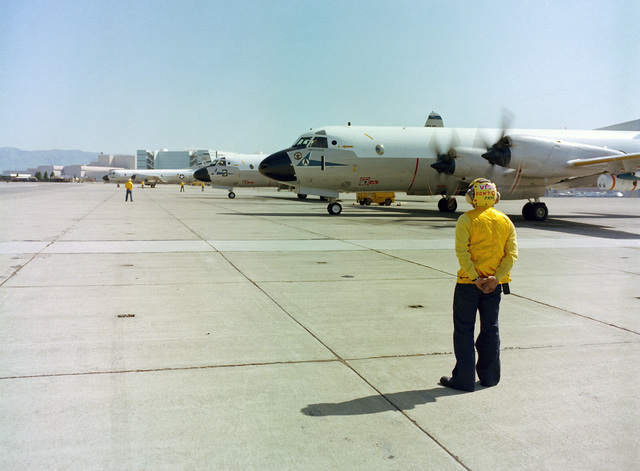A line crewman stands by as other crewmen direct the pilots of Patrol Squadron 50 (VP-50) P-3C Orion aircraft during the annual mine readiness certification inspection