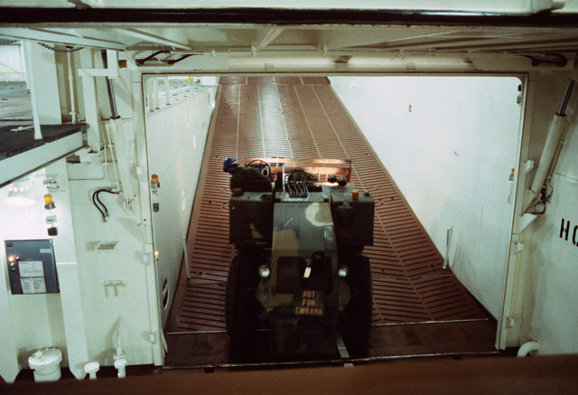 A materials handling forklift truck is driven up an interior ramp of the Waterman class maritime prepositioning ship SS PFC. EUGENE A. OBREGON. Equipment of the 6th Marine Amphibious Brigade is being loaded aboard the ship