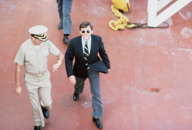A naval officer escorts Secretary of the Navy John F. Lehman Jr. on an inspection of the Waterman class maritime prepositioning ship SS PFC. EUGENE A. OBREGON. The ship is being loaded with equipment of the 6th Marine Amphibious Brigade