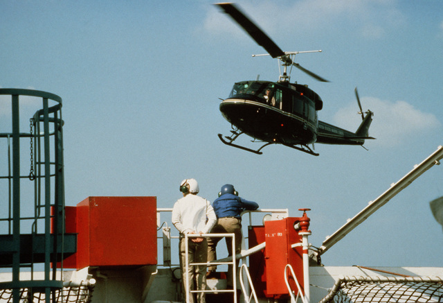 A US Marine Corps UH-1N Iroquois helicopter approaches for a landing on the helicopter platform of the maritime prepositioning ship SS PFC. EUGENE A. OBREGON. The helicopter is bringing Secretary of the Navy John F. Lehman Jr. for an inspection tour of the ship. Equipment of the 6th Marine Amphibious Brigade is being loaded aboard the ship