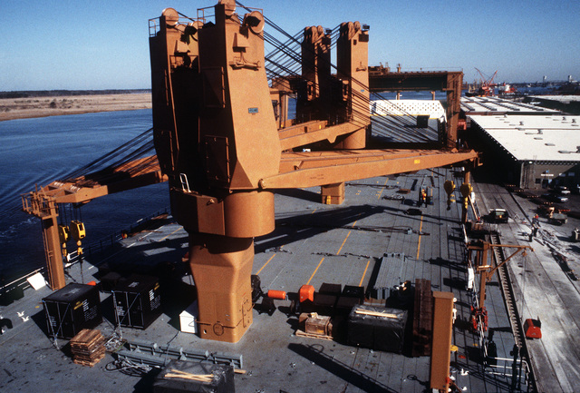 A view from the bridge, looking forward, at the Waterman class maritime prepositioning ship SS PFC. EUGENE A. OBREGON's (T-AK-3006) two sets of paired heavy lift cranes. The ship will be loaded with equipment of the 6th Marine Amphibious Brigade