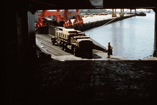 An M923 5-ton cargo truck tows an M353 trailer across the stern loading ramp of the Waterman class maritime prepositioning ship SS PFC. EUGENE A. OBREGON. Equipment of the 6th Marine Amphibious Brigade is being loaded aboard the ship