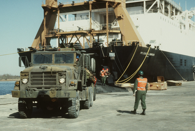 An M931 5-ton tractor is used to back a trailer onto the stern loading ramp of the Waterman class maritime prepositioning ship SS PFC. EUGENE A. OBREGON (T-AK 3006). Equipment of the 6th Marine Amphibious Brigade. is being loaded aboard the ship