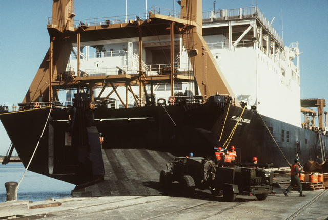 An MC4000 rough terrain forklift truck is used to tow a trailer-mounted generator up the stern loading ramp of the Waterman class maritime prepositioning ship SS PFC. EUGENE A. OBREGON (T-AK 3006). Equipment of the 6th Marine Amphibious Brigade is being loaded aboard the ship