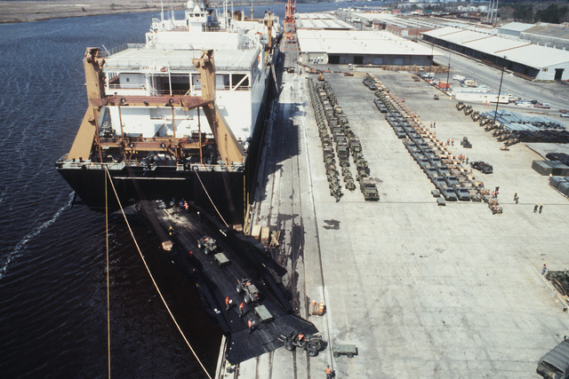 Forklift trucks are driven up the stern loading ramp of the Waterman class maritime prepositioning ship SS PFC. EUGENE A. OBREGON (T-AK 3006) during the loading of vehicles and equipment of the 6th Marine Amphibious Brigade. Other Marine equipment is staged on the wharf