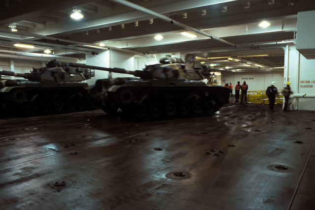 M60A3 main battle tanks are maneuvered into storage positions on the third deck of the Waterman class maritime prepositioning ship SS PFC. EUGENE A. OBREGON. The turret of the tank is traversed to the rear. Equipment of the 6th Marine Amphibious Brigade is being loaded aboard the ship