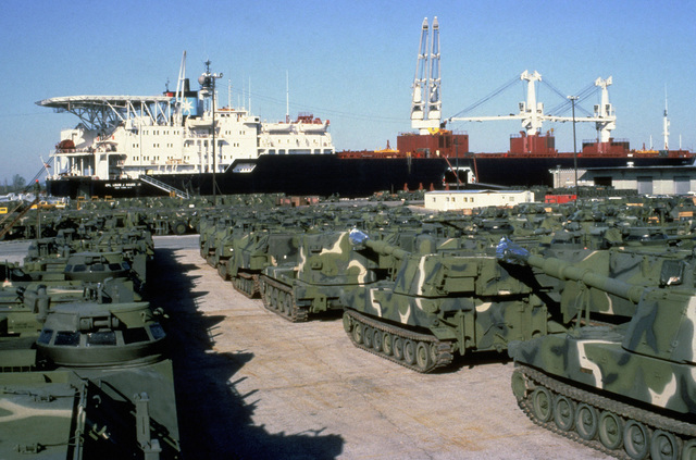 Personnel tracked landing vehicles, (LVTP7) and M109A2 155 mm self-propelled howitzers are staged on the wharf prior to being loaded aboard the Maersk class maritime prepositioning ship SS CPL. LOUIS J. HAUGE JR. The ship is being loaded with equipment of the 6th Marine Amphibious Brigade