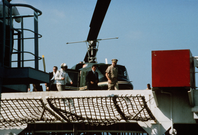 Secretary of the Navy John F. Lehman Jr. disembarks from a US Marine Corps UH-1N Iroquois helicopter on the helicopter platform of the Waterman class maritime prepositioning ship SS PFC. EUGENE A. OBREGON upon his arrival aboard for an inspection tour. Equipment of the 6th Marine Amphibious Brigade is being loaded aboard the ship