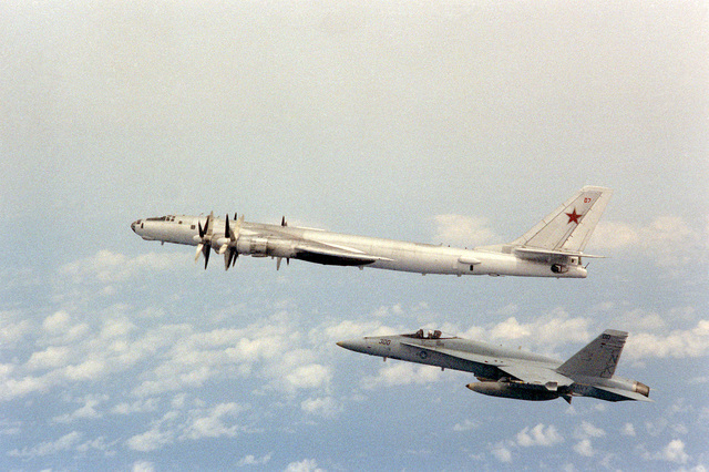 Air-to-air left side view of an F/A-18 Hornet aircraft from Strike-Fighter Squadron 113 (VFA-113) alongside a Soviet TU-142 Bear A aircraft (above)