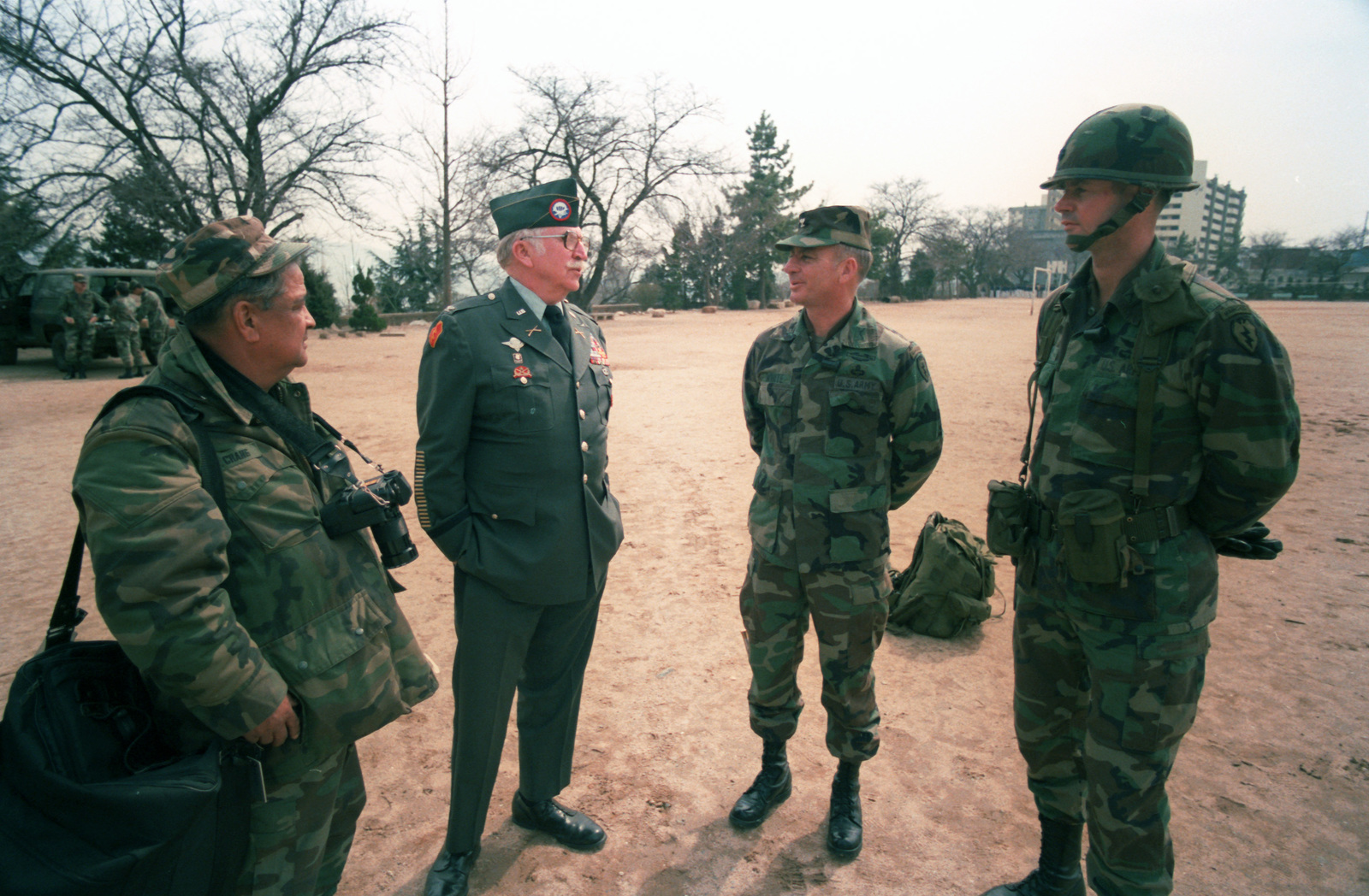 Retired Army Colonel (COL) Lewis Millett, a Korean War Medal of Honor recipient, left center, speaks with Colonel (COL) Jerry A. White, Commander, 1ST Brigade, 25th Infantry Division, and Lieuteant Colonel (LTC) George Close, Commander, 1ST Battalion, 5th  Infantry, 25th Infantry Division, right, after a ceremony commemorating the defense of Mason during the Korean War.  The ceremony is being held during the joint U.S/South Korean Exercise TEAM SPIRIT`85