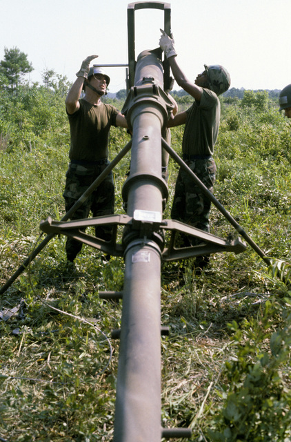 STAFF Sergeant Smith (left) and STAFF Sergeant York (right) erect the antenna mast for an AN/TRC-97 radio set