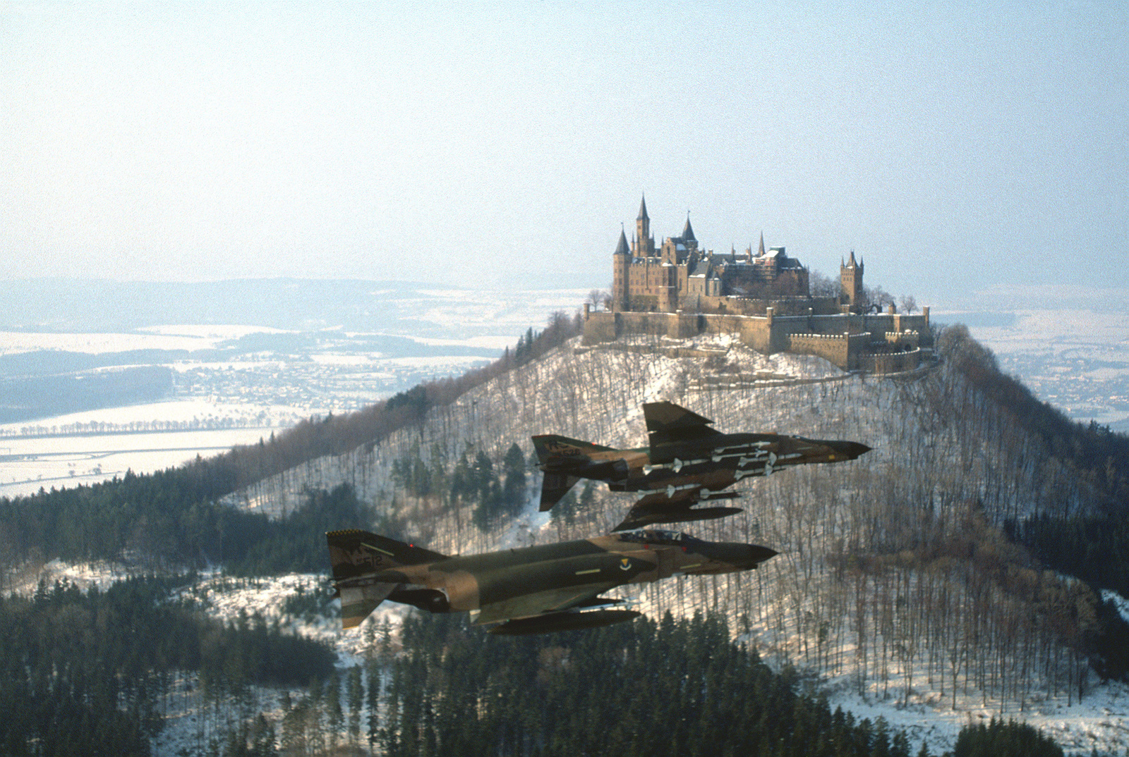 Two F-4E Phantom II aircraft assigned to the 512th and 526th Tactical Fighter Squadrons fly one of their last aerial missions over Castle Burg-Hollenzollern, near Ramstein Air Base. Both squadrons will replace their Phantoms with F-16 Fighting Falcon aircraft. Tail No. 512 is piloted by Lt. Col. Bruce Gillett and navigated by Capt. Mike Craig. Lt. Col. Tom Speelman is piloting tail No. 526 with 1st Lt. John Rogers navigating