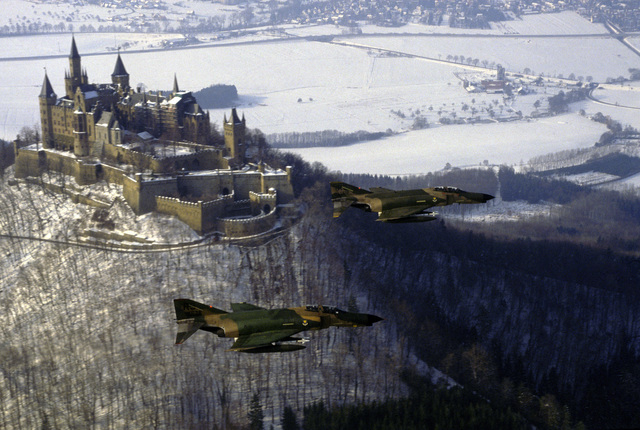 Two F-4E Phantom II aircraft assigned to the 512th and 526th Tactical Fighter Squadrons fly one of their last aerial missions over Castle Burg-Hollenzollern, near Ramstein Air Base. Both squadrons will replace their Phantoms with F-16 Fighting Falcon aircraft. Tail No. 512 is piloted by Lieutenant Colonel (LTC) Bruce Gillett and navigated by Captain (CPT) Mike Craig. LTC Tom Speelman is piloting tail No. 526 with 1st Lieutenant (1LT) John Rogers navigating