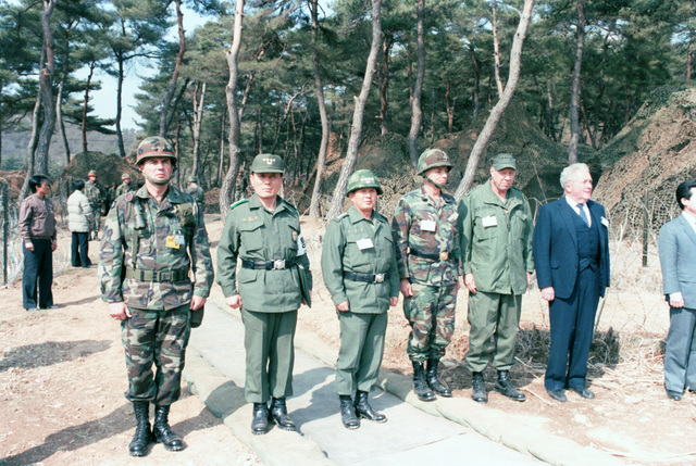 Standing near the helicopter pad as Korean President Chun Doo Hwan departs after observing the joint U.S./South Korean Exercise TEAM SPIRIT'85 are, left to right, Major General (MGEN) Claude M. Kicklighter, Commander, 25th Infantry Division, General Chung Ho Youg, Chief of Staff, Korean army; General (GEN) Lee Sang Hoon; General (GEN) William J. Livsey, Commander in Chief, United Nations Command; Admiral (ADM) William J. Crowe Jr., Commander in Chief, Pacific Fleet; and U.S. Ambassador to Korea Richard L. Walker